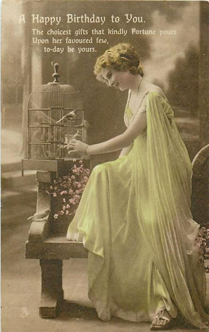 Een klassieke verjaardagskaart uit 1906 van de firma Tuck & Sons van een ingekleurde foto van een jongedame bij een vogelkooitje.
