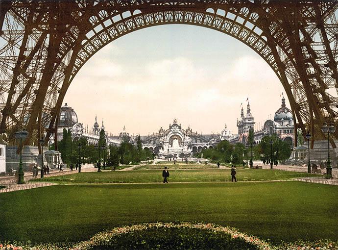 Een doorkijkje richting de entree van de Parijse wereldtentoonstelling, door de bogen van de Eiffeltoren, gebouwd ter gelegenheid van de wereldtentoonstelling van 1889. Fotochroom uit 1889 [Publiek domein].