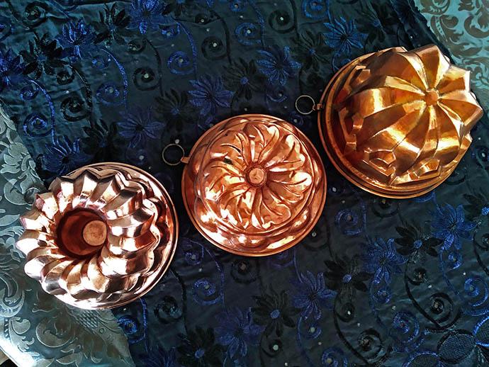 Drie koperen bakvormen in verschillende kleuren na het bakken. Foto © My inner Victorian.